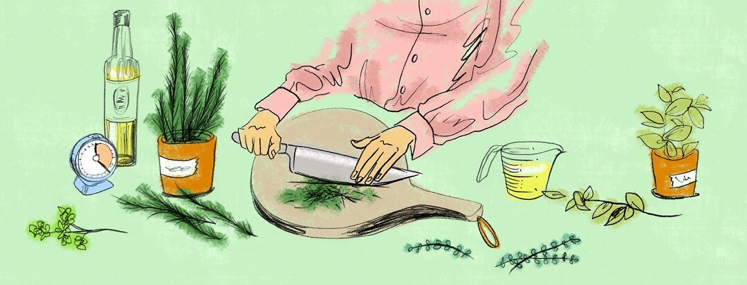 a woman in the kitchen chops fresh herbs from her herb garden